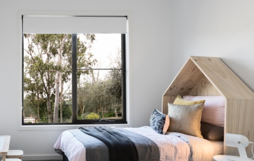 Bedroom with bed and window with roller blind