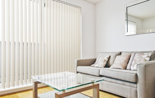 Large window with Russells vertical blind next to couch and coffee table
